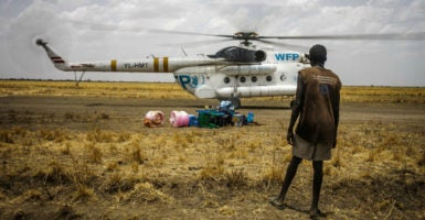 A World Food Program helicopter delivers relief as an onlooker waits in Jonglei State, South Sudan. (Photo: Maciej Moskwa/ZUMA Press/Newscom)