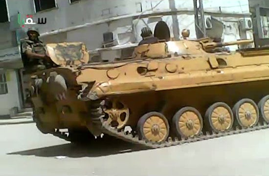 An image grab taken from a video uploaded on YouTube on April 9, 2012 shows a Syrian soldier sitting atop a tank as troops deploy in Saqba on the outskirts of Damascus.