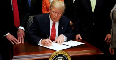 President Donald Trump signs an executive order aimed at killing the Obama administration's contentious clean water rule, Feb. 28, 2017. (Photo: Polaris /Newscom)
