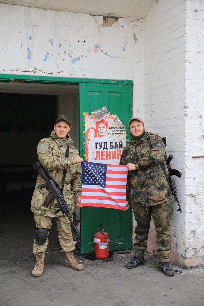 "Ukrainian Azov Battalion soldier Ivan Kharkiv (right) and another soldier in front of a poster that says ""Bye, Bye Lenin."" (Photo courtesy Ivan Kharkiv)"
