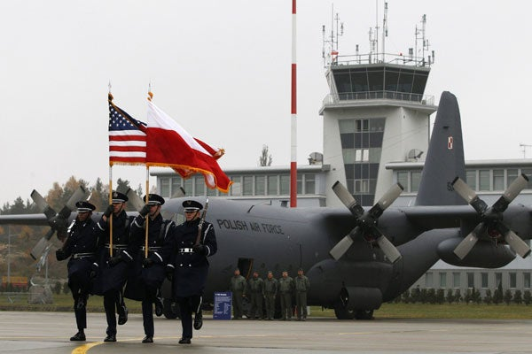 U.S. soldiers carry flags of both Poland and the United States during the opening ceremony of the first United States Air Force (USAF) aviation detachment in Poland. (Photo: Reuters/Newscom)