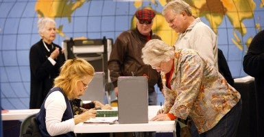 Pollworker Karen Siegel, left, checks in voter Sharon Kerbs during election day in Wisconsin. (Photo: Newscom)