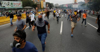 Opposition supporters clashed with riot police on Thursday while rallying against Venezuelan President Nicolas Maduro, who has tried to consolidate power to himself amid an ongoing economic collapse. (Photo: Carlos Garcia Rawlins/Reuters/Newscom)