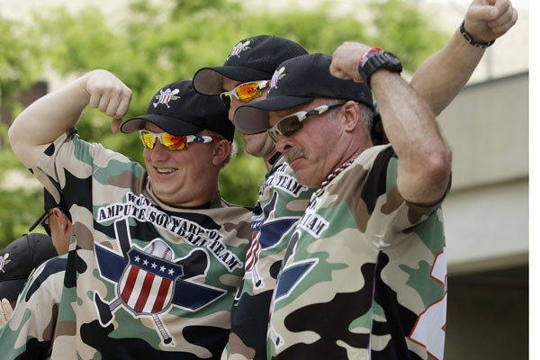 Wounded Warrior Amputee Softball Team members (L-R) Josh Wege, Matt Kinsey, and Todd Reed pose on a parade platform during a Memorial Day Parade in Binghamton, New York May 28, 2012. (Photo: Reuters/Newscom)