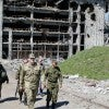 People walk past debris of a destroyed building near Donetsk Airport just outsid