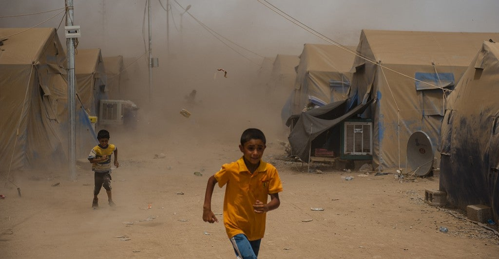 Children run as a sandstorm hits a refugee camp for those who fled the ISIS threat in Mosul, Iraq. (Photo: Martin Alan Smith/Pacific Press/Newscom)