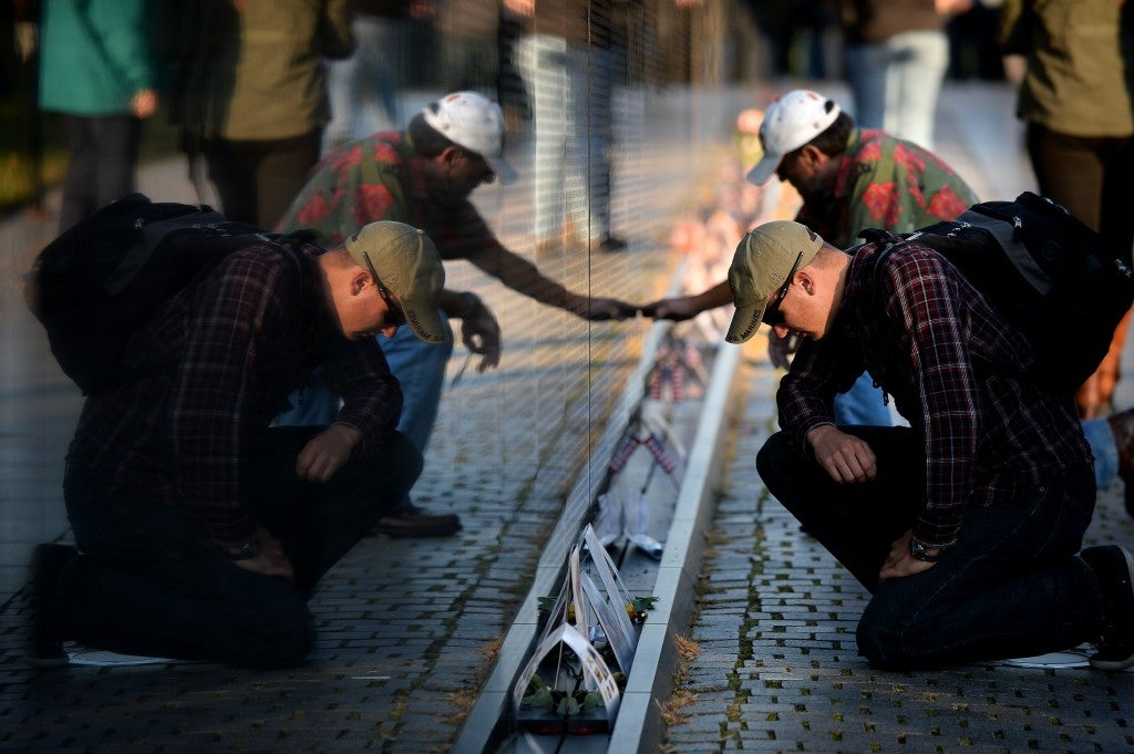 Curently serving US Marine Mark Best from Boston pays his respect on the wall of the Vietnam Veterans Memorial. (Photo: Olivier Douliery/Newscom)