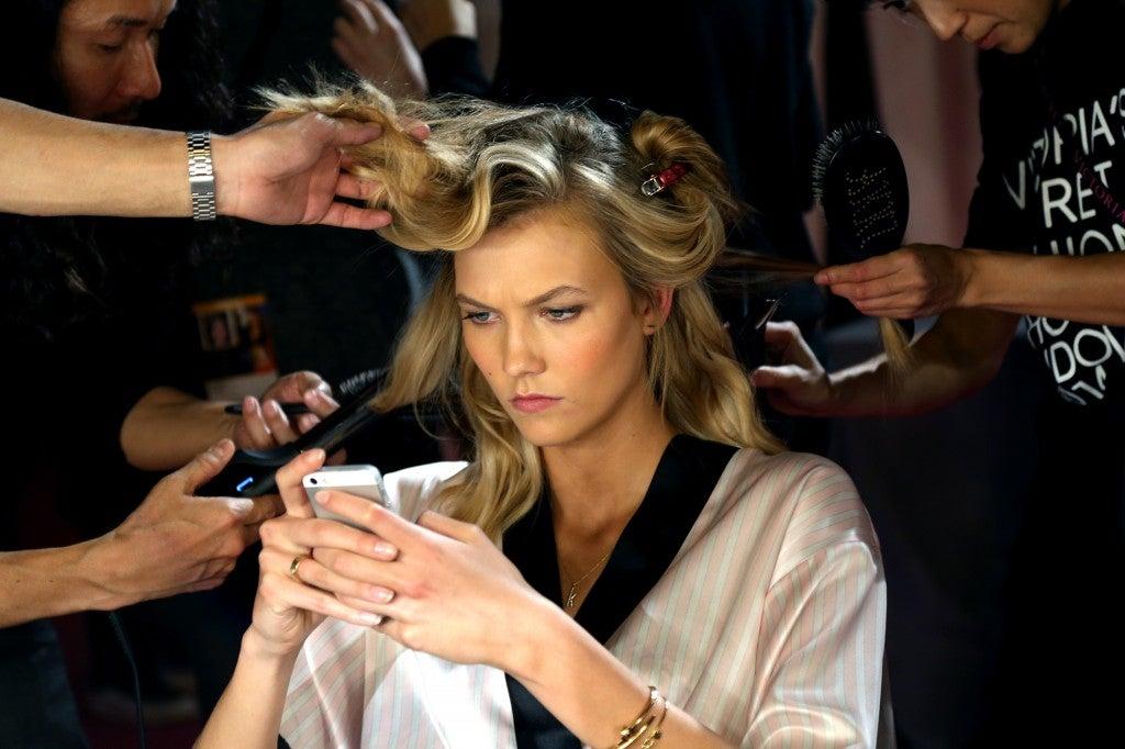 Model Karlie Kloss gets her hair and make up done prior to the show. (Photo: Hugo Philpott/Newscom)