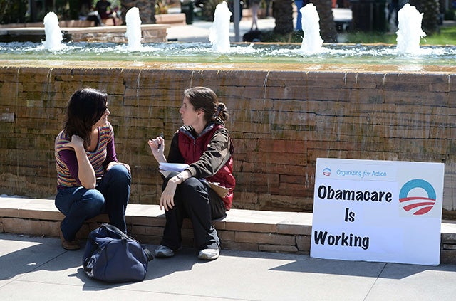 An ACA supporter (R) talks with a student (L) about Obamacare on the campus of Santa Monica City College in Santa Monica, California in October 2013. (Photo: Robyn Beck/AFP/Getty Images/Newscom)