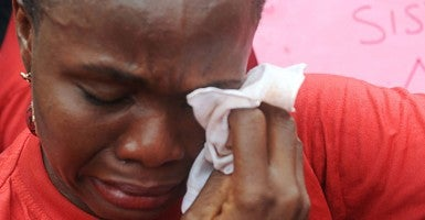One of the mothers of the missing Chibok school girls wipes her tears as she cries during a rally by civil society groups pressing for the release of the girls. (Photo: PIUS UTOMI EKPEI/AFP/Getty Images/Newscom) width=