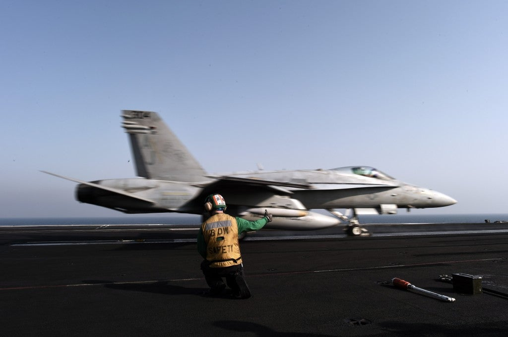 An F/A-18C hornet takes off for Iraq from the flight deck of the aircraft carrier USS George H.W. Bush on August 14, 2014 in the Persian Gulf. (Photo: Mohammed Al-Shaik/Newscom)