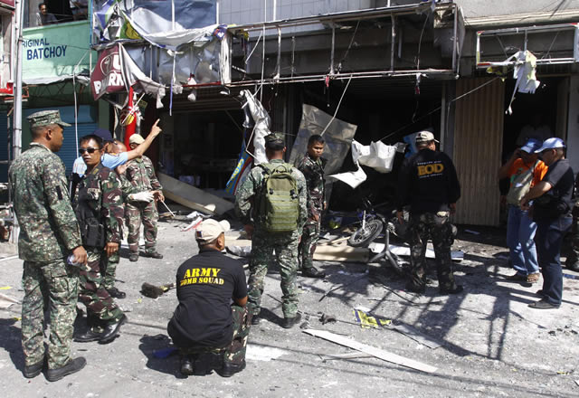 Armed Forces of the Philippines investigators inspect the site of a bomb blast in Cotabato City, southern Philippines August 2, 2011. Suspected Muslim militants believed to be associated with the Jemaah Islamiyah group bombed a gun store in Cotabato City, killing two people and injuring nine others on the second day of Islam's holy month of Ramadan, the military said.