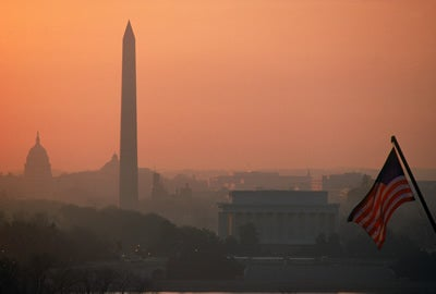 Silhouetted Lincoln Memorial, Washington Monument and Capitol Building with American flag at sunrise in Washington DC