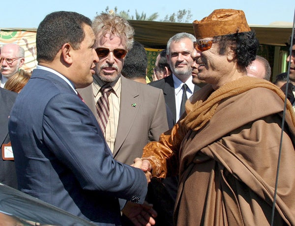 Venezuelan President Hugo Chavez (L) shakes hands with Libyan leader Moammar Qadhafi in Tripoli Wednesday 17 May 2006.