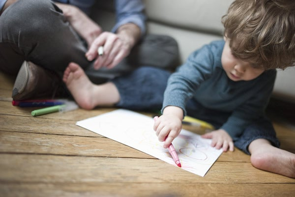Young boy sits on floor with parent and draws