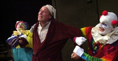 A Christmas Carol is in production by the River Stage at Cosumnes River College in Sacramento. Seen here is a scene from the play as the Ghosts of Christmas Presents, dressed as clowns, do a tug of war with Scrooge. Credit: Jose M. Osorio/ZUMA Press/Newscom