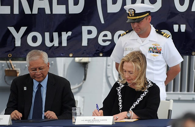 Secretary of State Hillary Clinton (R), beside Philippine Foreign Affairs Secretary Alberto del Rosario (L), signs a declaration marking the 60 years since the United States signed a security treaty with the Philippines on board the USS Fitzgerald, a US Navy destroyer, docked at the Manila bay on November 16, 2011.