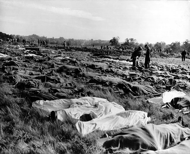 Hundreds of dead soldiers in stretchers covered with a blankets after D-Day. Killed during Normandy landings, they lie in a temporary cemetery on the cliff of Colleville-sur-Mer, overlooking Omaha Beach, ca. June 8-10, 1944. This scene took place a little west of the permanent Normandy American Cemetery and Memorial. France, World War 2. (Photo: Newscom)