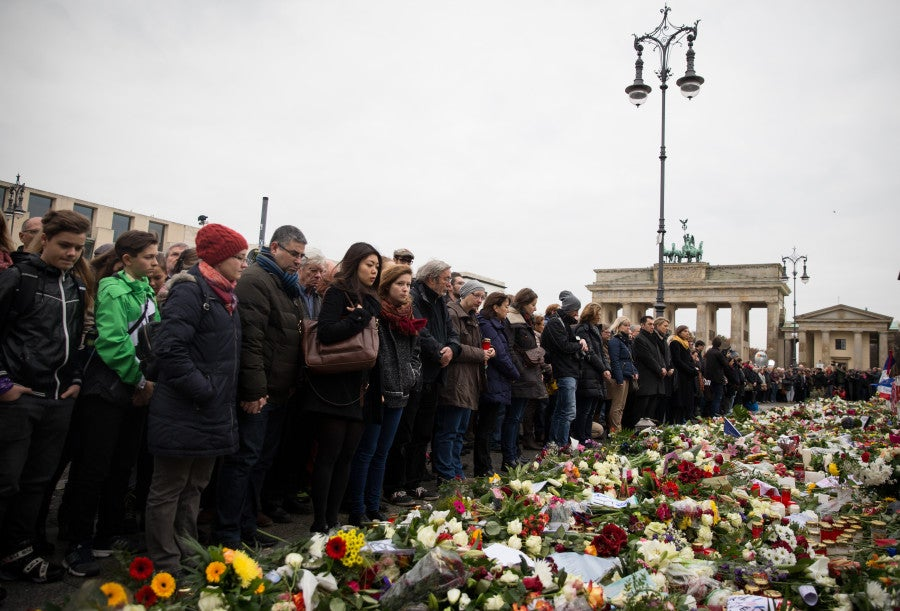 Citizens participate in a Europe-wide minute of silence for the victims of the terror attacks in Paris at the Brandenburg Gate in front of the French Embassy in Berlin,Germany. (Photo: Newscom)
