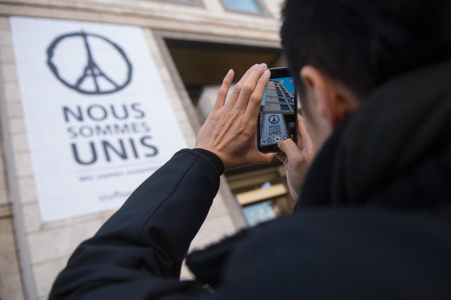 "A giant poster, featuring a peace sign with the eiffel tower and the writing ""Nous sommes unis"" -- ""we stand united"" is hung on the wall of the town hall in Stuttgart, Germany. The image, by French artist Jean Julien, has gone viral since the attacks. (Photo: Marijan Murat/Newscom)"