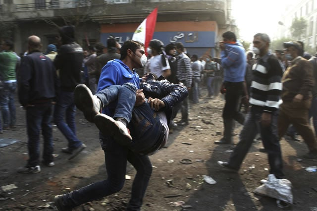 A protester carries another affected by tear gas thrown by police during clashes between protesters and police near Tahrir Square in Cairo November 22, 2011.