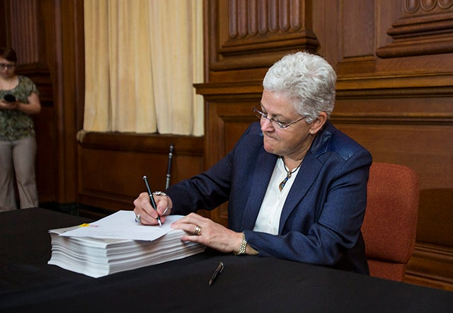 EPA administrator Gina McCarthy signs President Obama's new carbon pollution emission guideline plan at EPA headquarters in Washington, DC, USA, 02 June 2014. The plan, which bypasses Congress, calls for a 30 percent cut in carbon emissions by 2030.  (Photo: Newscom)