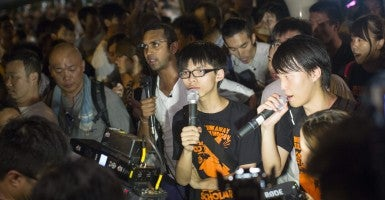 Joshua Wong, center, listens as another protester speaks amid a Hong Kong pro-democracy march. (Photo: Newscom)
