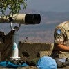 U.N. 'peacekeepers' use high-powered binoculars to watch fighting near the Syrian town of Quneitra. (Photo: Atef Safadi/Newscom)