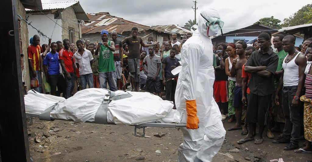 Liberian burial squad carries the body of a suspected Ebola victim. (Photo: Newscom)