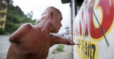 On Nov. 4, Filipino typhoon survivor Domingo Realino applies paint on a sign board in Anibong village. The village was severely damaged by the 2013 Typhoon Haiyan in Tacloban City. One year after Haiyan left nearly 8,000 people dead or missing in the eastern Philippines, many survivors are still suffering from emotional distress despite being busy with physically rebuilding their lives. (Photo: Dennis M. Sabangan/Newscom)