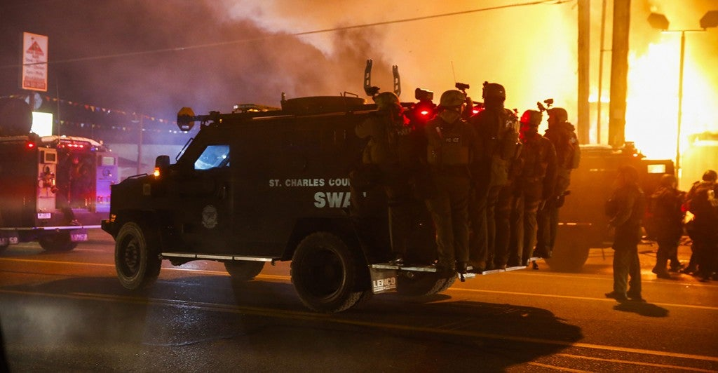 Police ride on a vehicle past a burning building. (Photo: Tannen Maury/Newscom)