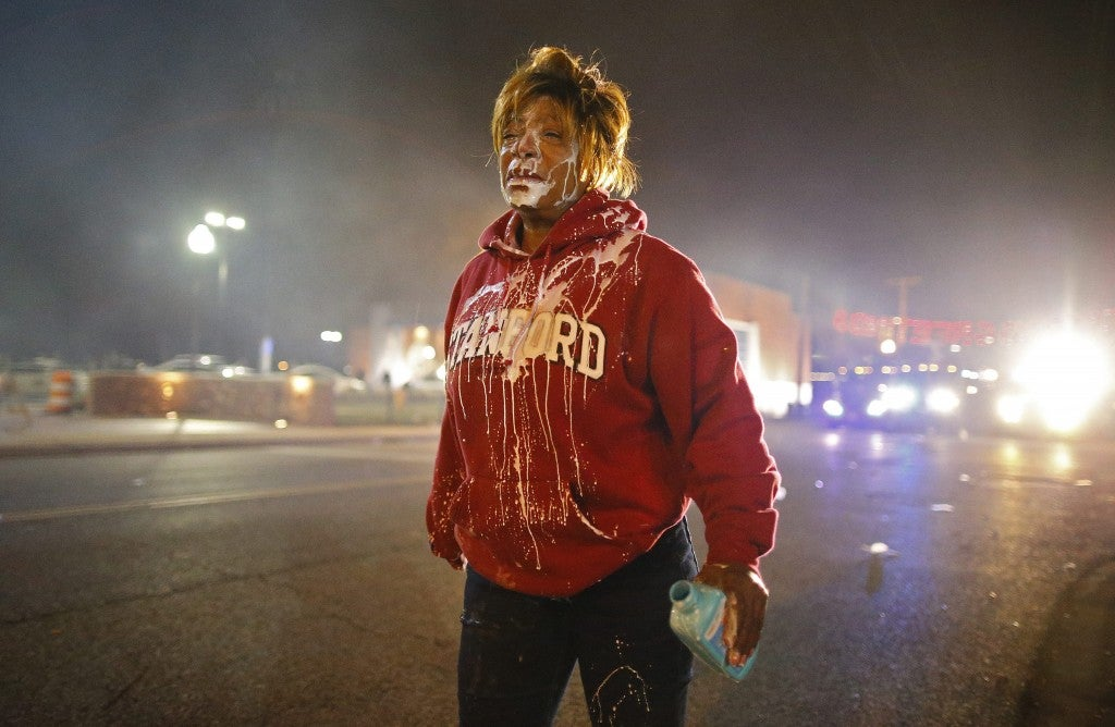 A protestor walks down the street after getting tear gas in her face. (Photo: Larry W. Smith/Newscom)