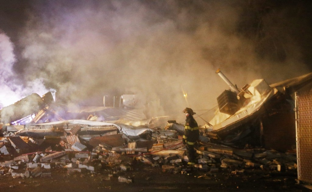 A firefighter stands next to smoking rubble after protesters burned more buildings. (Photo: Larry W. Smith/Newscom)