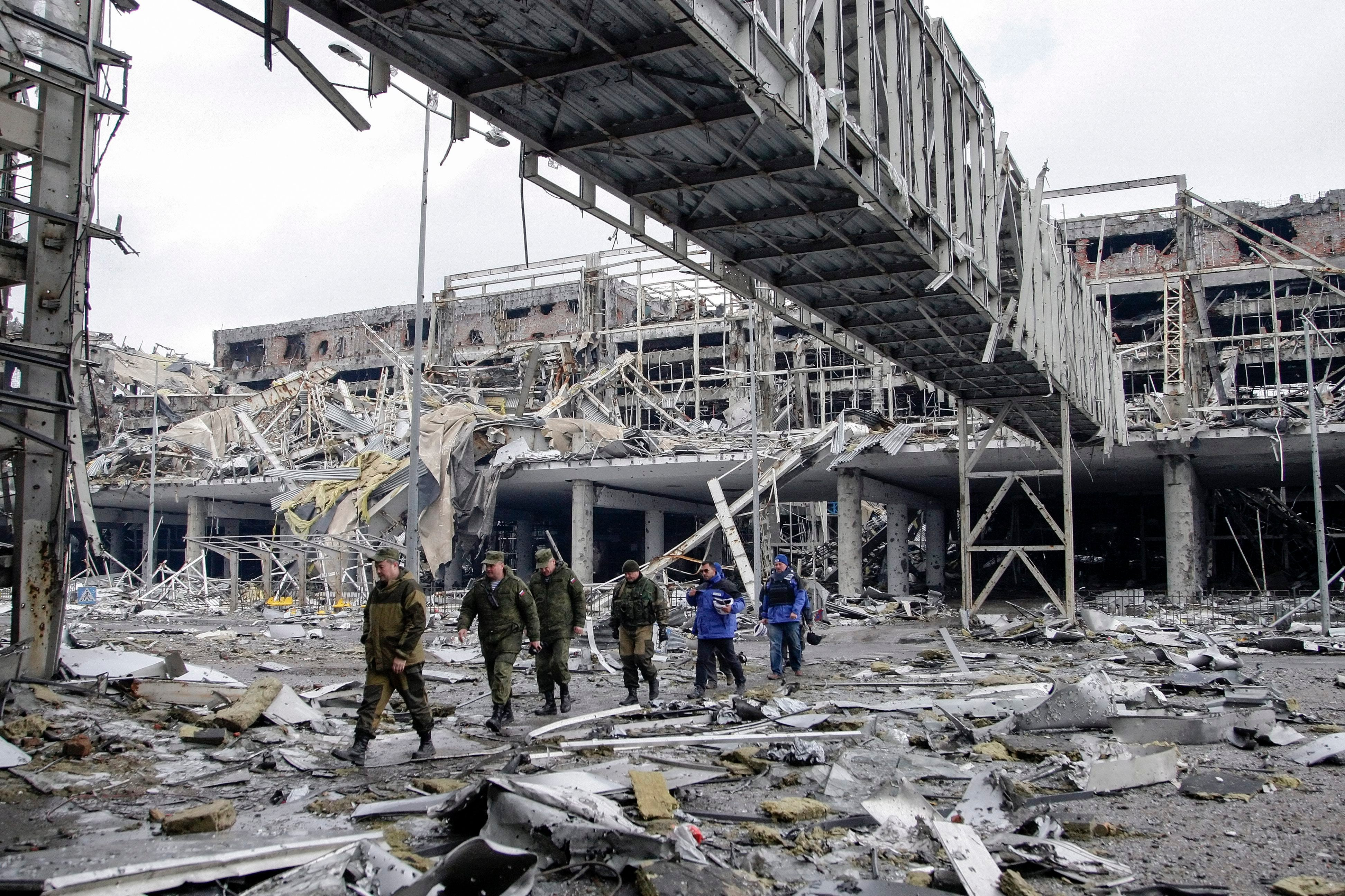 Pro-Russian separatists together with OSCE observers walk at the destroyed Donetsk International Airport, in Donetsk, Ukraine, on April 4. (Photo: Newscom)
