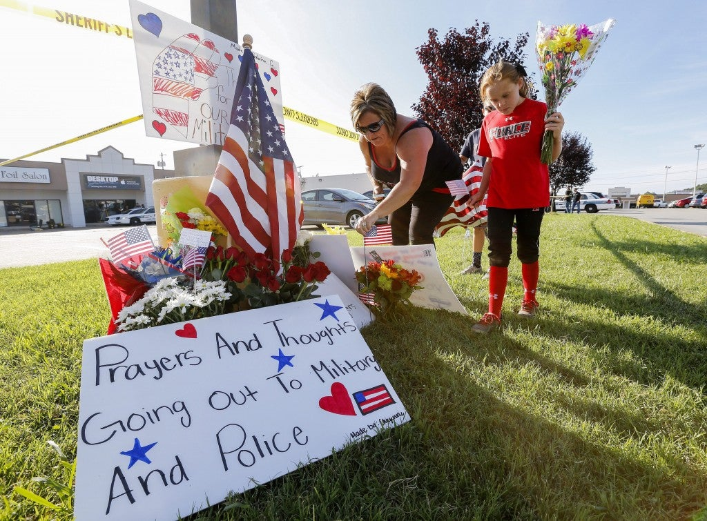 epa04849689 A family brings flowers to a makeshift memorial near a US Military Recruiting storefront after a shooting in Chattanooga, Tennessee, USA, 16 July 2015. Authorities say the shootings at two different locations left four US Marines and the gunman Mohammod Youssuf Abdulazeez dead.  EPA/ERIK S. LESSER (Newscom TagID: epalive751891.jpg) [Photo via Newscom]