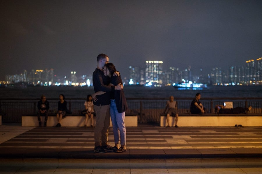 Mourners hug each other during a vigil in Hong Kong, China. (Photo: Jerome Favre/Newscom)