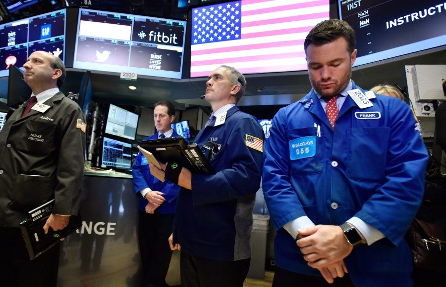 Traders pause on the floor of the New York Stock Exchange during a moment of silence for the victims at the start of the trading day in Manhattan. (Photo: EPA/Justin Lane/Newscom)