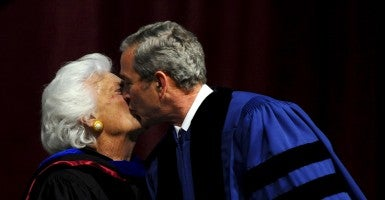 President George W. Bush kisses his mother Barbara Bush on stage to give the Commencement Speech at Texas A&M University in College Station, Texas. (Photo: Newscom)