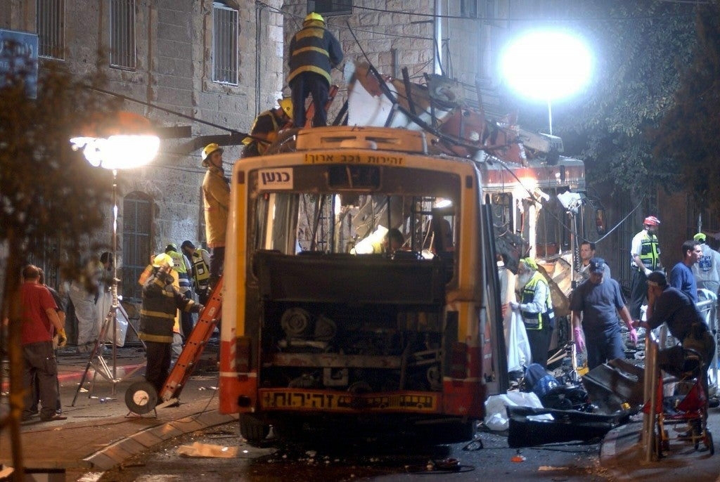 Israeli emergency personnel inspect the scene of the massive Palestinian suicide bus bombing in western Jerusalem on August 19, 2003. (Photo: Rusty Stewart/Newscom)