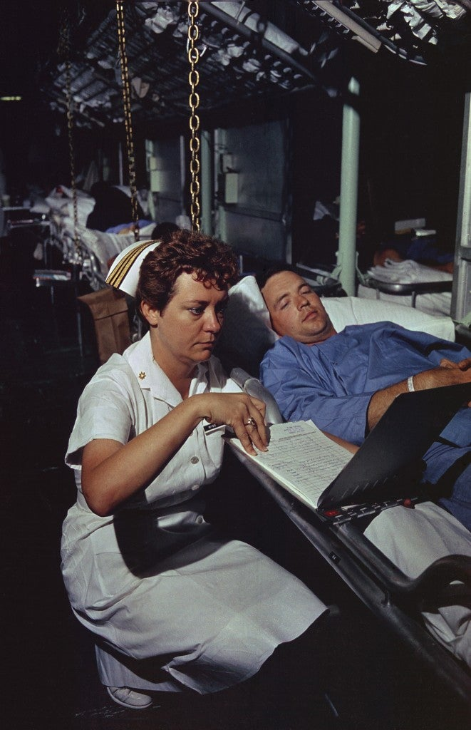 Lieutenant Commander Dorothy Ryan, an Navy Nurse aboard the hospital ship USS Repose off South Vietnam, checks a wounded soldier's medical chart. April 4, 1966. (Photo: evhistorypix/Newscom)