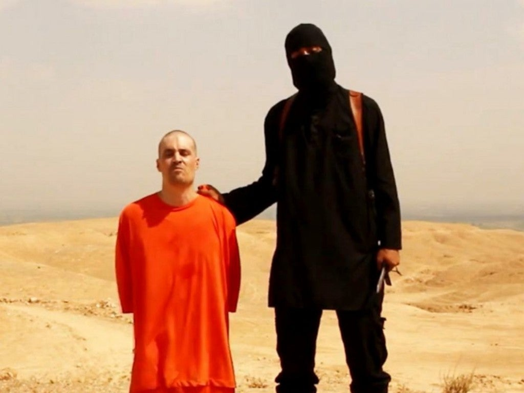 A videograb shows a masked ISIS militant holding a knife speaks next to U.S. journalist James Foley. (Photo: Newscom)