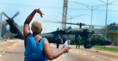 A woman waves for the National Guard to be evacuated during a rescue operation for Hurricane Katrina victims. (Photo: Gerardo Mora/EPA/Newscom)