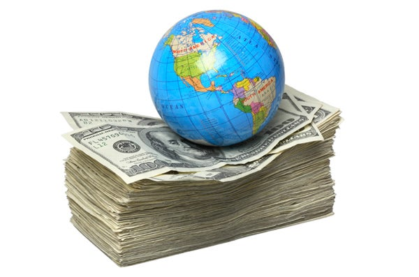 Globe, Earth, sits on pile of cash, money