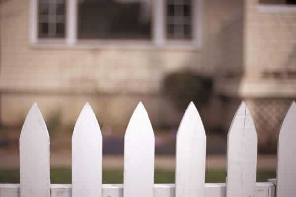 White picket fence in front of house / home