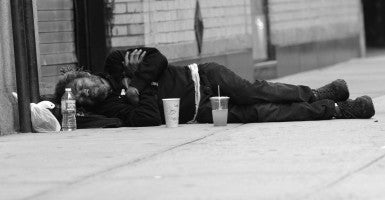 A homeless man seen sleeping on a West 51st Street sidewalk in Manhattan. (Photo: Doug Meszler / Splash News/Newscom / Edited: Daily Signal)