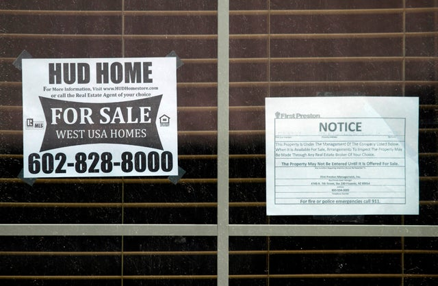 A Housing and Urban Development home for sale sign is displayed in the window of a home in Chandler Heights, Arizona
