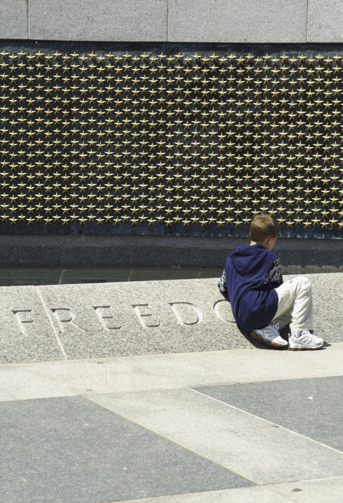 A young tourist takes in the sacrifice and honor at the memorial. (Photo: Getty Images)