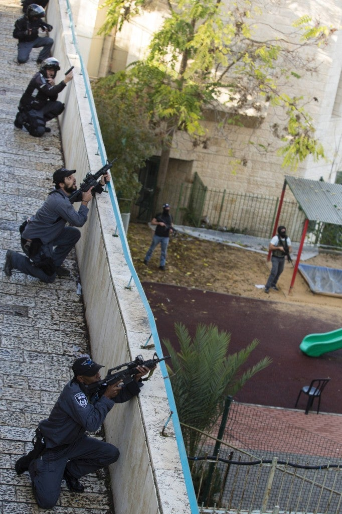 Israeli policemen take position near the scene of an attack in a Synagogue in on Nov. 18. (Photo: Newscom)