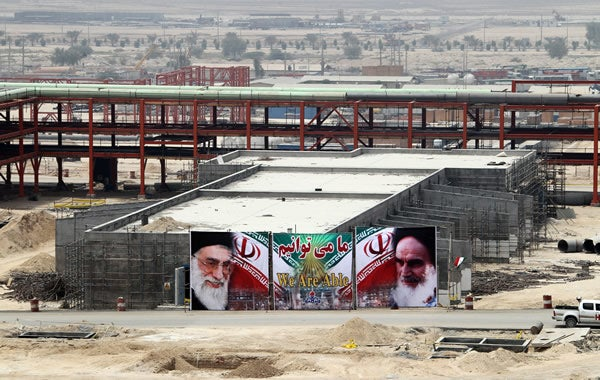 Banner bearing of Iran's Ayatollah Ali Khamenei hangs over Iranian oil field.