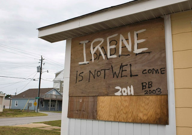 A plywood shutter, covering a window of a beachside house, shares a message from a community preparing for the arrival of Hurricane Irene in Atlantic Beach